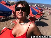Shameless brunette shows her tits on a beach